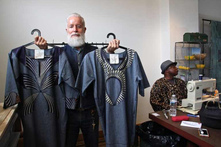 Bryan Norris, founder of the Refugee Makers Project in Lancaster, holds two caftans, which creator Remmy Kasongo calls bubus.