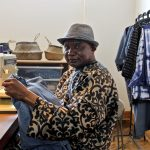 Congolese refugee Remmy Kasongo works at his sewing machine at the Refugee Makers Project in Lancaster, sewing caftans he calls bubus, made of indigo dyed fabrics. (Emma Lee/WHYY)