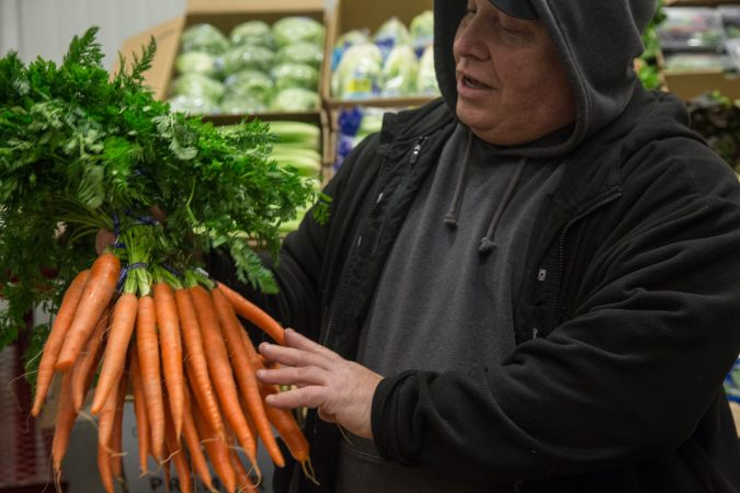 Jimmy Iovine, 58, inspects a bunch of carrots. It's important to Jimmy that he buys the best product for his customers. (Emily Cohen for WHYY)
