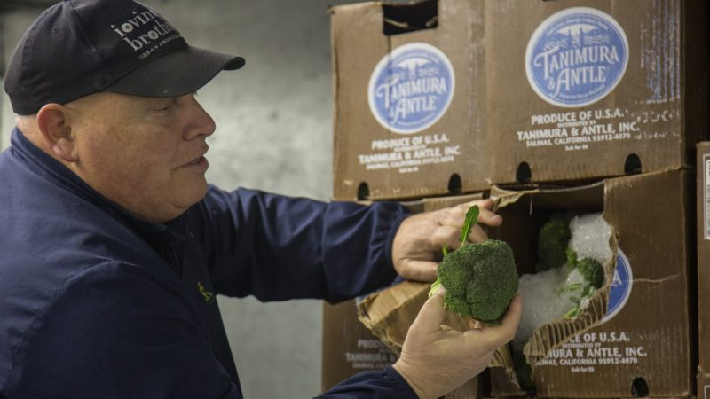 Jimmy inspects some of the broccoli he just purchased after it arrives back at his market. (Emily Cohen for WHYY)