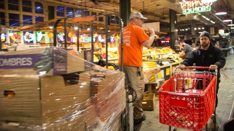 At 5:30 a.m., the setup is in full swing with workers building up the shelves as other continue to bring produce up from the basement. (Emily Cohen for WHYY)