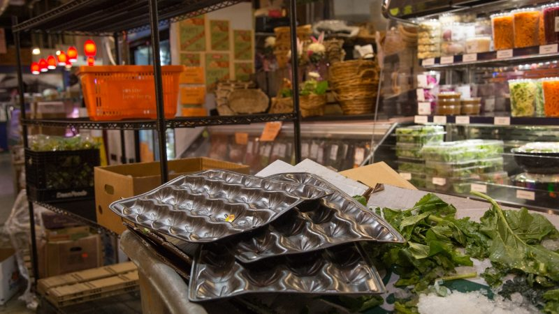 Cardboard and waste are stacked at the front of the market after the produce has been placed on their shelves. (Emily Cohen for WHYY)