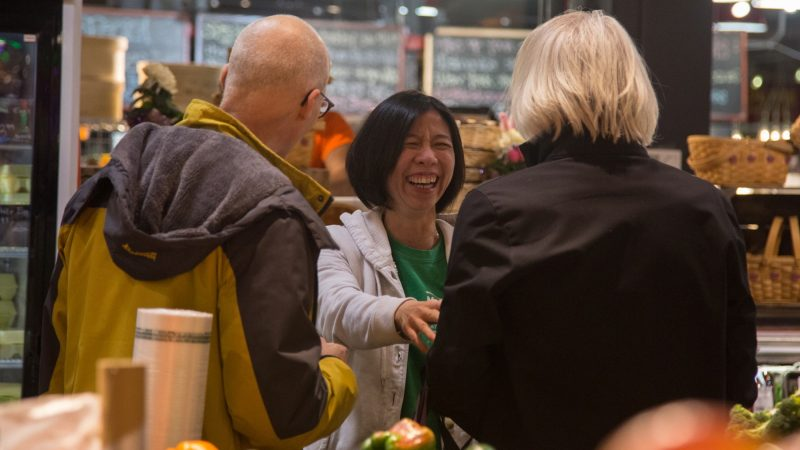 Lily Winoto, 47, the store manager (center) laughs with some regulars as they shop at Iovine Brothers Produce. (Emily Cohen for WHYY)
