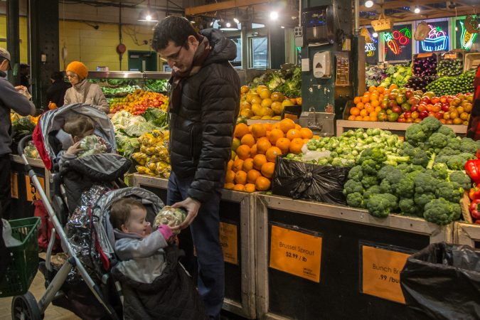 "Joseph Domingo of Rittenhouse hands a head of cauliflower to one of his 20-month-old twins. ""It's a good experience for the kids, the colors and the different types of veggies, it's a learning experience,"" he explains. (Emily Cohen for WHYY)"