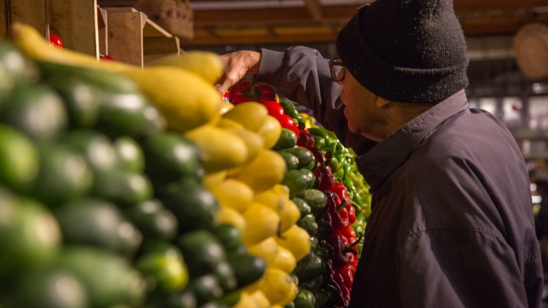 A shopper picks up some produce in the precisely stacked shelves of Iovine Brothers. (Emily Cohen for WHYY)