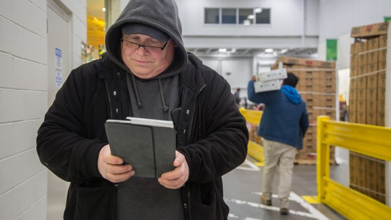 After making a purchase at one of the many vendors at the wholesale center, Jimmy enters the information into his Google Sheets document as he walks to the next vendor. (Emily Cohen for WHYY)
