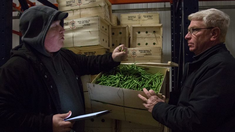 Jimmy checks the freshness of some green beans alongside Vassallo Produce owner David DiPascale, 57, in their back refrigerator. (Emily Cohen for WHYY)