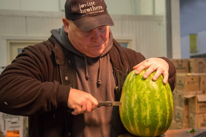 Watermelons are just coming into season, so Jimmy cuts into one to inspect the freshness and taste before deciding to buy a whole box of them. (Emily Cohen for WHYY)