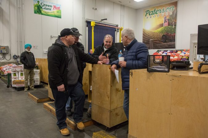 Jimmy chats with some other buyers and vendors about a new trucking policy that may affect their prices and businesses. (Emily Cohen for WHYY)