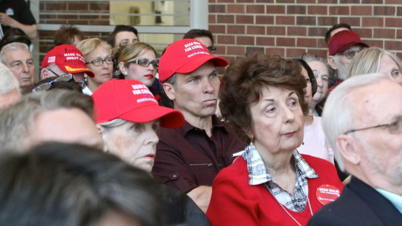 Supporters of Dean Malik for Congress wear Trump-style caps saying