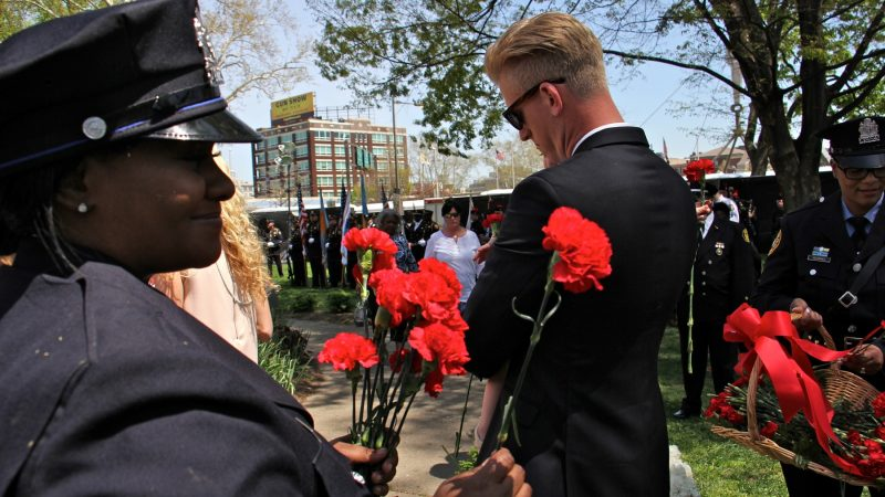 Police officers and firefighters hand out red carnations to participants in the Living Flame Memorial Service. (Emma Lee/WHYY)