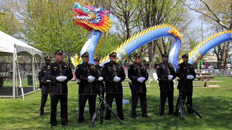 The Philadelphia Police and Fire Honor Guard stand at ease during the memorial ceremony, set against the backdrop of the Chinese Lantern Festival in Franklin Square. (Emma Lee/WHYY)