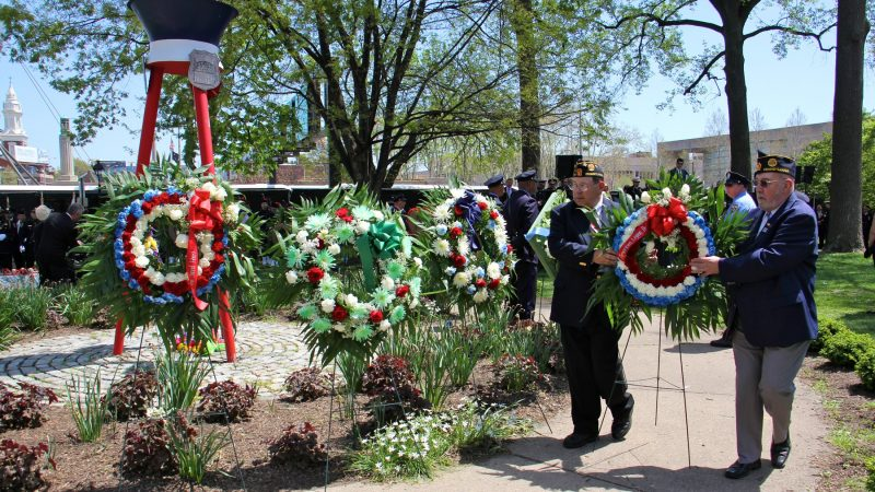 Civic organizations surround the Living Flame Memorial with wreaths in honor of Philadelphia police officers and firefighters who died in the line of duty. (Emma Lee/WHYY)
