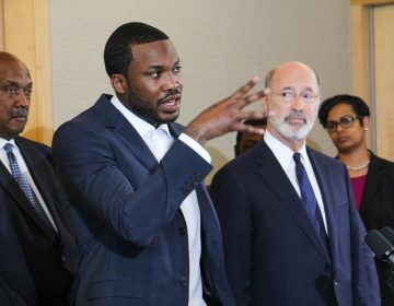 Rapper Meek Mill talks criminal justice reform with Pennsylvania Gov. Tom Wolf during a press conference at the National Constitution Center.