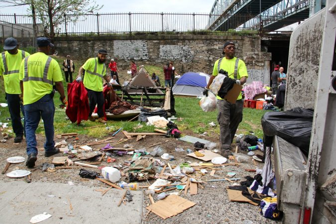 Sanitation workers clear away mounds of garbage from a heroin encampment at Lehigh and Kensington avenues. (Emma Lee/WHYY)