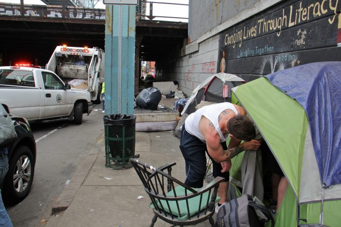 A visitor to the Kensington Avenue heroin encampment checks on a friend. (Emma Lee/WHYY)