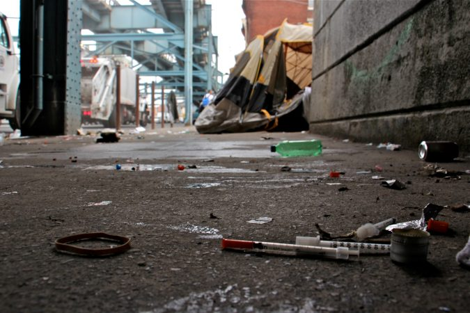Needles litter the area under the Conrail tracks on Kensington Avenue. (Emma Lee/WHYY)