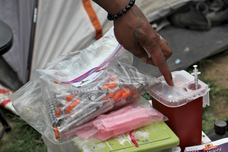 A resident of the Kensington Avenue encampment shows how he safely disposes of his used needles. (Emma Lee/WHYY)