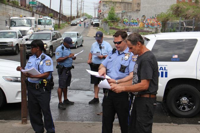 Police hand out flyers at Kensington Avenue and Tusculum Street, ordering residents of the heroin encampment there to leave by May 30. (Emma Lee/WHYY)