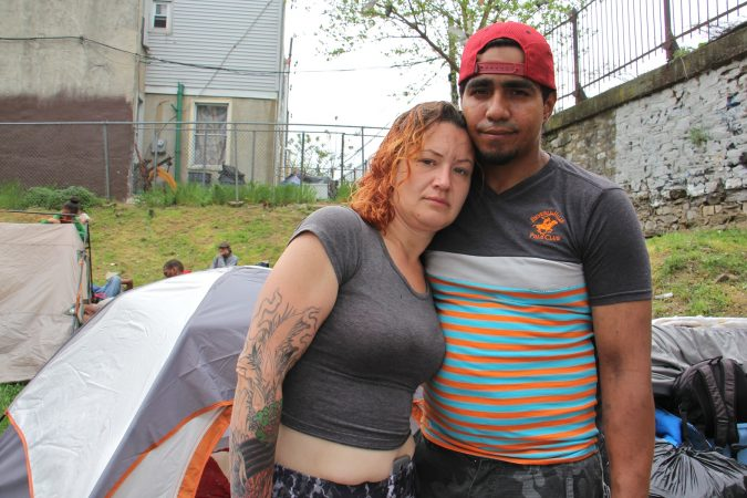 Salvatore Gonzalez and his fiancée stand in front of their tent near the Kensington Avenue railroad overpass, where heroin addicts have taken shelter since camp along the Conrail tracks near Gurney Street was shut down. (Emma Lee/WHYY)