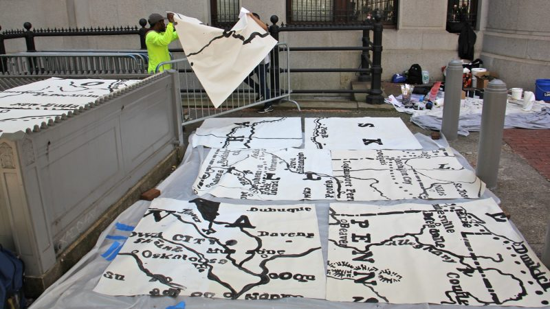 Mural Arts workers lay out painted pieces of the Octavius Catto mural. (Emma Lee/WHYY)