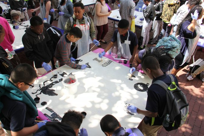 Students from Dunbar Promise Academy and other Philadelphia schools participate in the painting of the Octavius Catto mural during a community painting session at City Hall. (Emma Lee/WHYY)