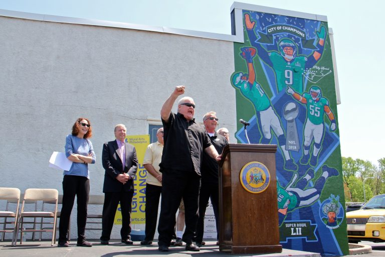 Retired football player Bill Bergey leads fans in an E-A-G-L-E-S chant at the dedication of a David McShane mural at Spike's Trophies in Northeast Philadelphia commemorating the team's Super Bowl win.