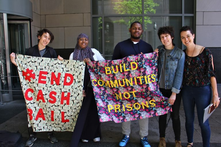 Activists with the Philadelphia Community Bail Fund (from left) Milo Giovanniello, Veronica Rex, David Harrington, Eli Hadley and Cara Tratner, stand outside the Criminal Justice Center, while inside, members of the group posted bail for 15 women as part of Mama's Bailout Day. (Emma Lee/WHYY)