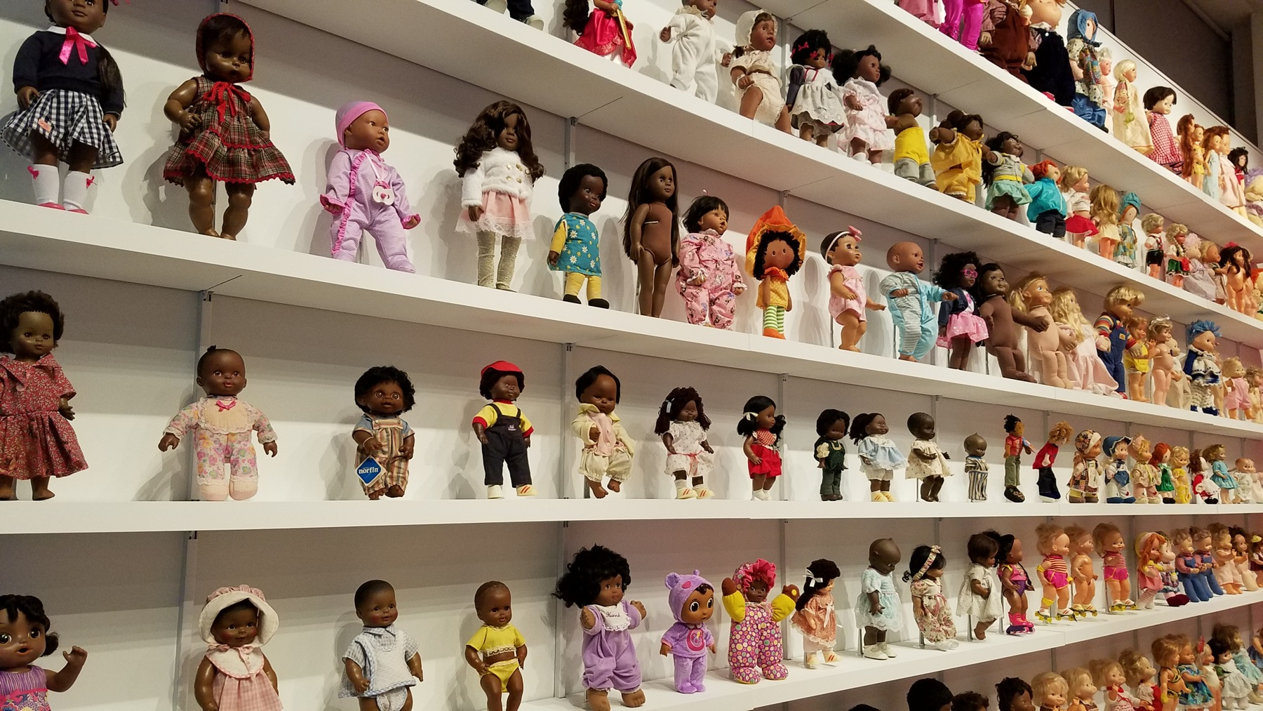 Whiteman's dolls, on the left side of the wall, are all black. Hancock's on the right are all white.