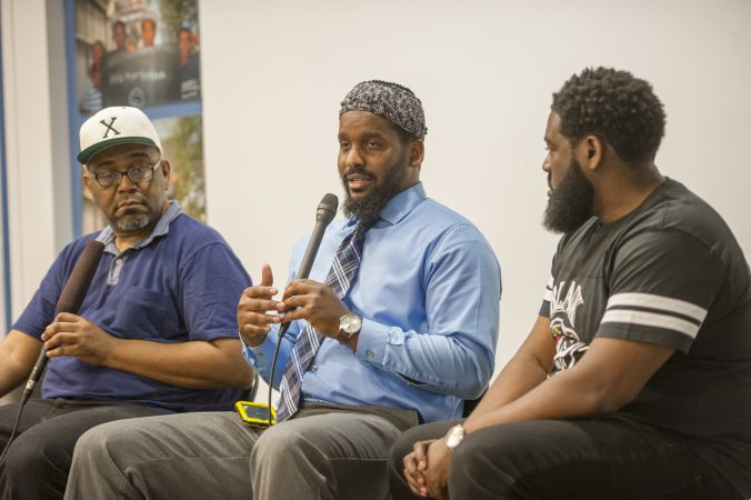 Moderator Michael Dennis, (left), Mujahideen Mohammed, and B. F. Nkrumah, (right), share their insights with the audience. (Jonathan Wilson for WHYY)