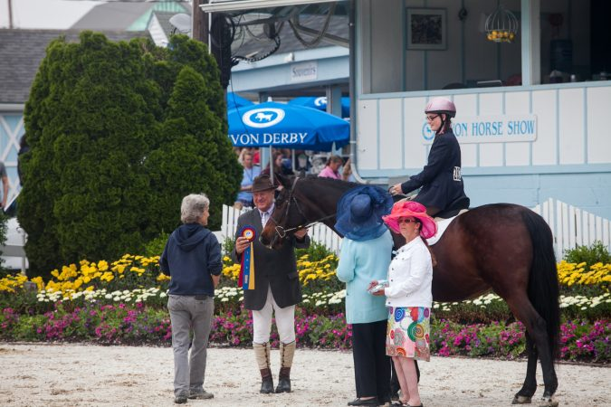A rider is given a ribbon after competing at the Devon Horse Show Sunday, May 27. (Brad Larrison for WHYY)