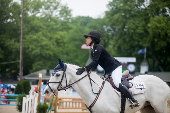 Hallie Rush rides her horse Sky Miles at the 122nd annual Devon Horse Show Sunday, May 27. (Brad Larrison for WHYY)
