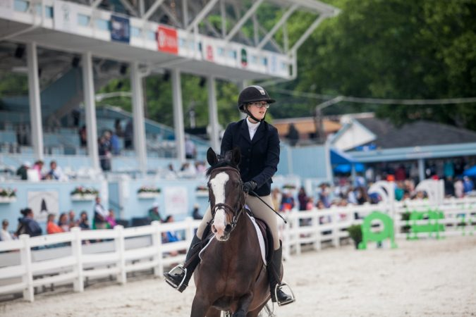 Catherine Sweeney rides her horse, Can Fly, through the course Sunday at the Devon Horse Show. (Brad Larrison for WHYY)