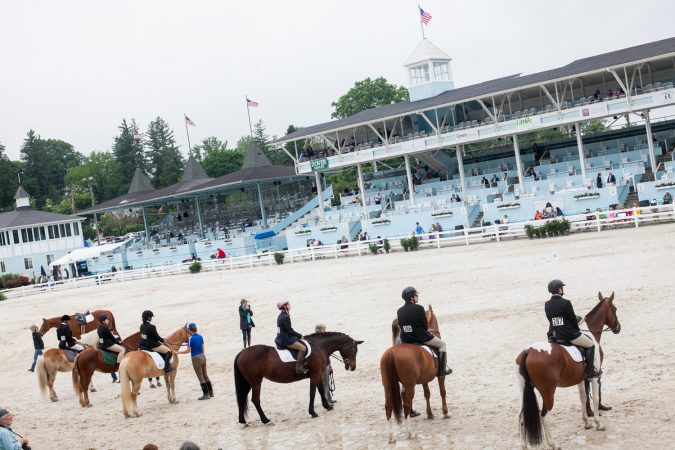 Riders line up in the main oval at the Devon Horse Show Sunday, May 27. (Brad Larrison for WHYY)