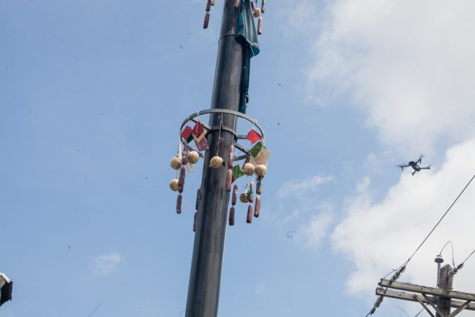 Prizes hang from the top of the grease pole at the Italian Market Festival as a drone hovers nearby Sunday. (Brad Larrison for WHYY)
