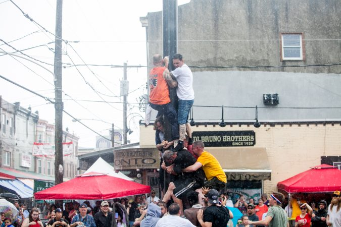 As a heavy rain started to fall the South Philly team who has competed in past years tries to climb the grease pole anyway. (Brad Larrison for WHYY)