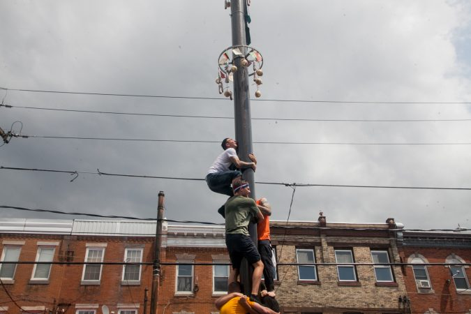 Nick Cordisio climbs on to his teammates shoulders as he tries to make it to the top of the grease pole. (Brad Larrison for WHYY)
