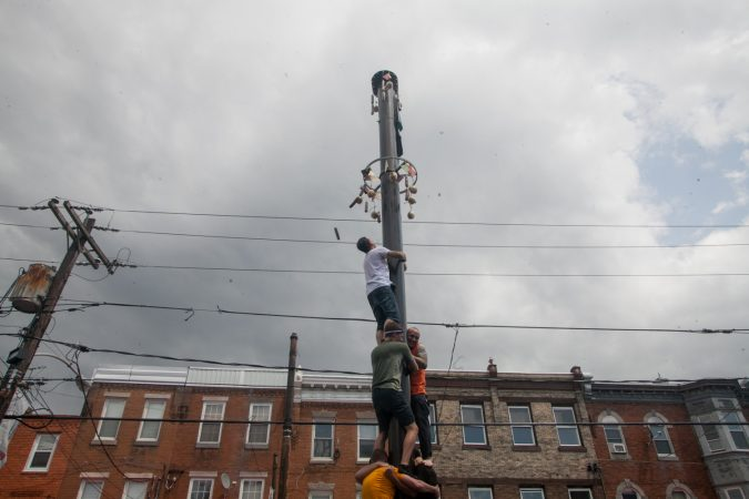 Nick Cordisio climbs on to his teammates shoulders and tosses a piece of cured meat that hung from the top of the grease pole. (Brad Larrison for WHYY)