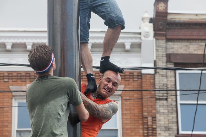 Escher, of the South Philly team, get his head stepped on by teammate Chris Cordisio Sunday as they ascended the grease pole. (Brad Larrison for WHYY)