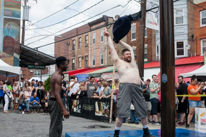 Tyler Dallas, left, and Mike Sirera were the first two volunteers to attempt the grease pole contest at the Italian Market Festival Saturday. (Brad Larrison for WHYY)