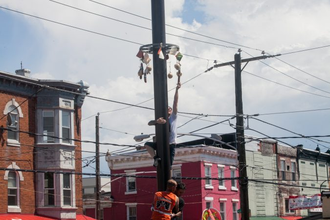 Nick Cordisio climbs on to his teammates shoulders and grabs a piece of cured meat that hung from the top of the grease pole. (Brad Larrison for WHYY)