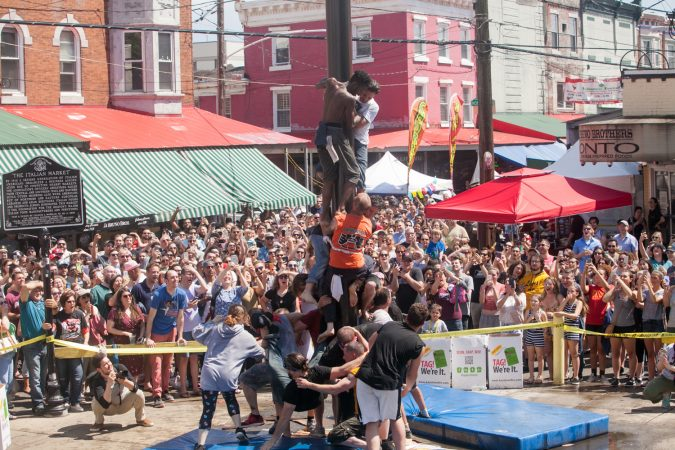 Team South Philly made another attempt at ascending the grease pole Sunday at the Italian Market Festival. (Brad Larrison for WHYY)
