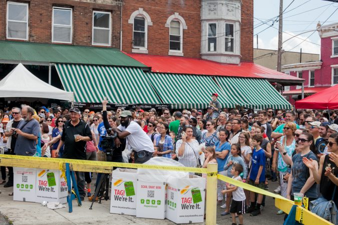 A large crowd cheered as the first impromptu team of climbers attempted to ascend the grease pole at the Italian Market Festival. (Brad Larrison for WHYY)