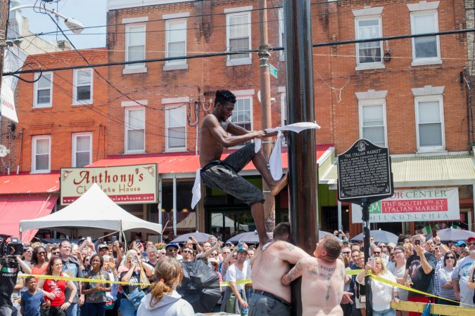 Tyler Dallas of South Philadelphia attempts to ascend the grease pole at the Italian Market Festival Sunday. (Brad Larrison for WHYY)