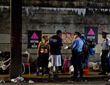 Philadelphia police speak to residents of a homeless encampment at Kensington and Lehigh avenues before a scheduled clean out.(Kimberly Paynter/WHYY)
