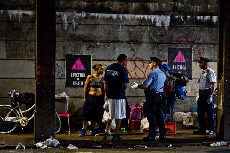 Philadelphia police speak to residents of a homeless encampment at Kensington and Lehigh avenues before a scheduled clean out in May 2018. (Kimberly Paynter/WHYY)