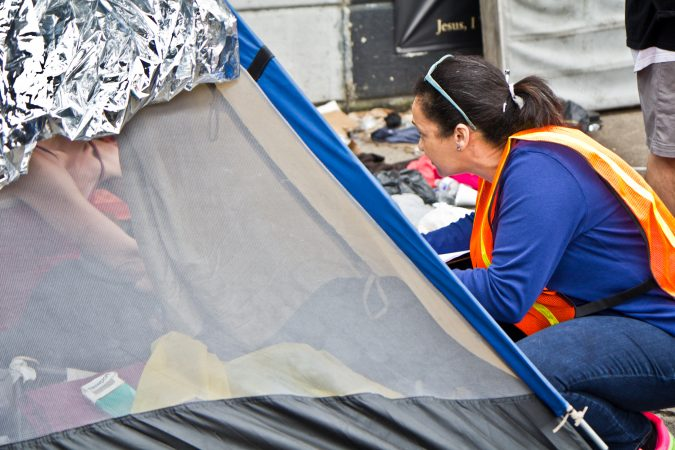 An outreach worker speaks to residents of a homeless encampment at Kensington and Lehigh avenues about half an hour before a scheduled clean out. (Kimberly Paynter/WHYY)