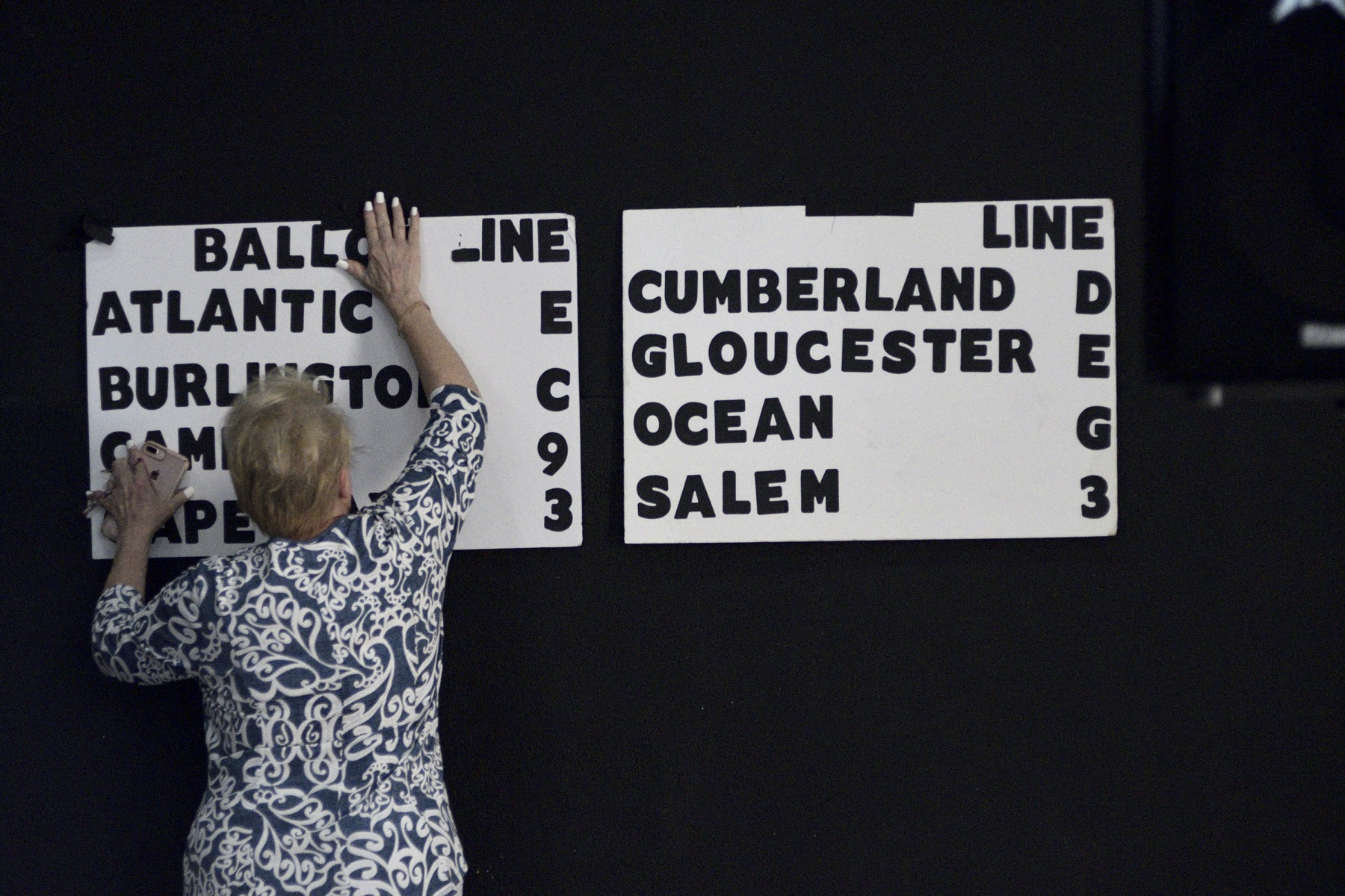 Campaign volunteer Helen Duda mounts a board indicating the candidate's position on the eight different ballots for the upcoming congressional primaries.