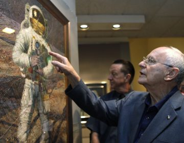 In this July 15, 2009 file photo, Apollo 12 astronaut Alan Bean walks through the largest exhibition of his artwork to date, inspired by his experience walking on the moon, to celebrate the 40th anniversary of the first Apollo moon landing, in Washington. Bean, the Apollo and Skylab astronaut, fourth human to walk on the moon and an accomplished artist, has died.  (Jacquelyn Martin/AP Photo, File)