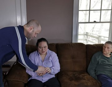 In this March 5, 2018 photo, Wil Darcangelo, (left), speaks with his 22-year-old adopted daughter, Lavender, who is blind and autistic, while friend and housemate, Christoph Malvaney, listens at their home.